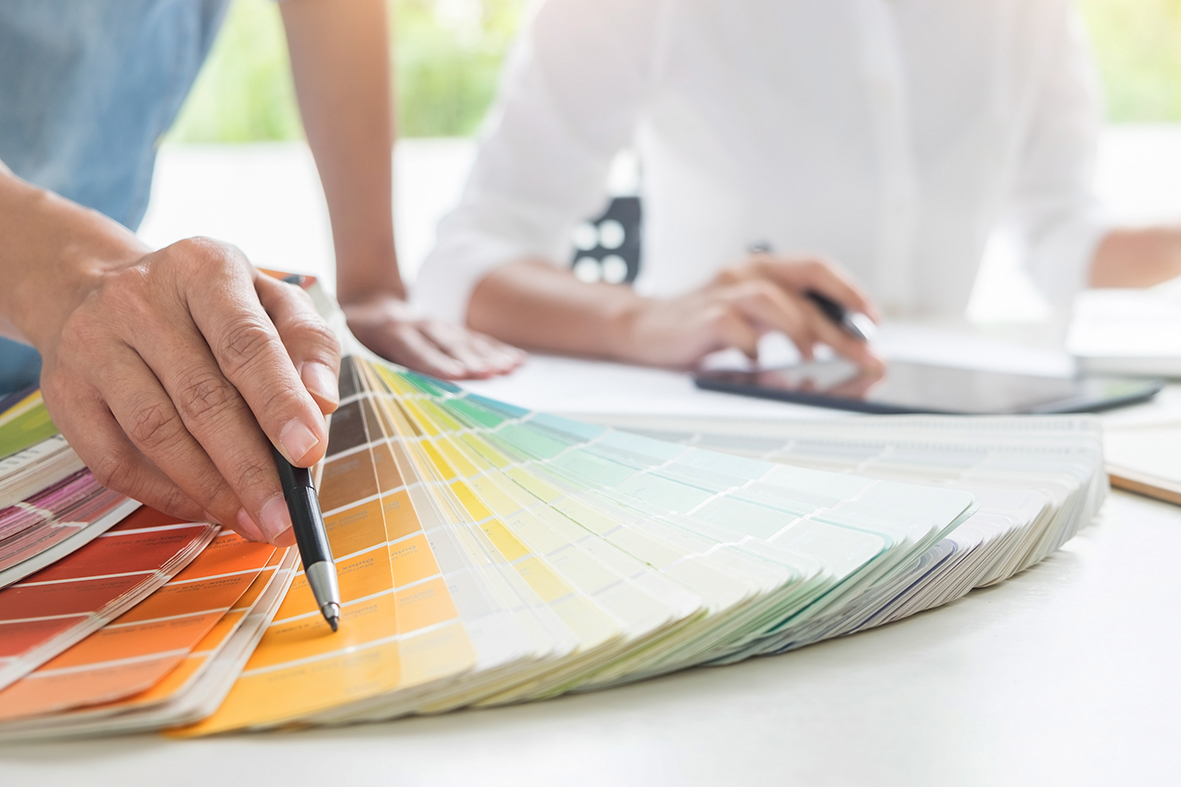Creative or Interior designers teamwork with pantone swatch and building plans on office desk, architects choosing color samples for design project