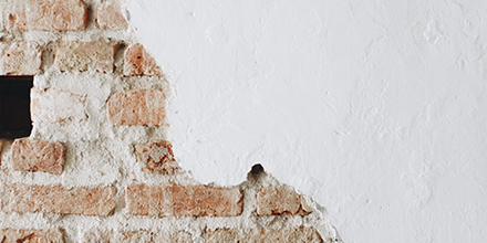 A cracked concrete white wall with bricks